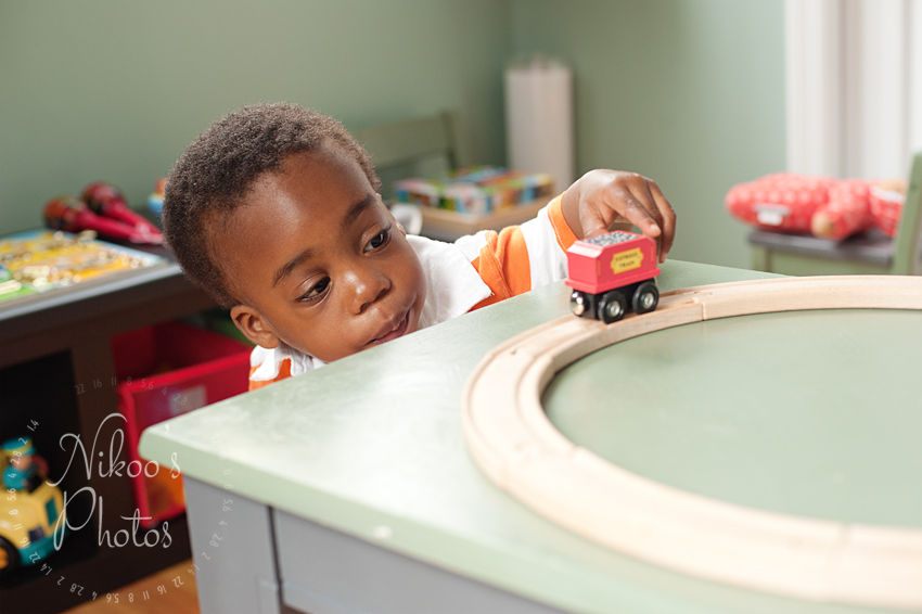 Portrait of a two-year-old boy playing with his train set