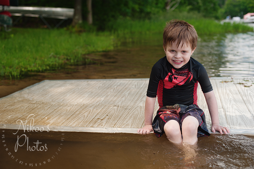 A portrait of a little boy hanging out on the dock at Deep Creek Lake, Maryland